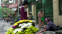 Flowers with at the background a woman selling and cutting fish Stock Footage