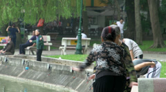People working out at the bank at the Hoàn Kiếm Lake Stock Footage