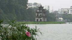 Pink flowers with Tháp Rùa (Turtle Tower) in Hoàn Kiếm Lake Stock Footage