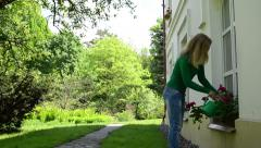 Attractive woman with watering-can water flowers in summer Stock Footage