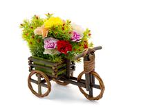Wooden bicycle with colorful carnations on white Stock Photos