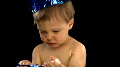 A white baby boy wears a party hat and blows a noise maker Stock Footage