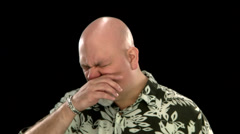A fat bald white man sneezes into a tissue Stock Footage