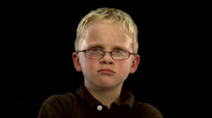 A young blonde boy makes a grumpy face - stock footage
