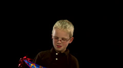 A young blonde boy puts on a party hat Stock Footage