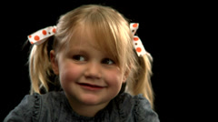 A  young blonde girl with pigtails blows a kiss to the camera Stock Footage