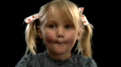 A  young blonde girl with pigtails covers her mouth with her hands Stock Footage