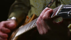 Close up of a mans hand strumming the strings of a guitar Stock Footage