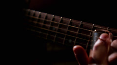 Close up of the neck of a guitar and a man fingering the frets Stock Footage