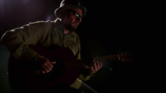 A spot light hits a guitar player on a stool Stock Footage