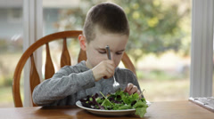Boy eating a salad Stock Footage