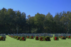 Military gravestones decorated with wreaths cemetery Stock Footage