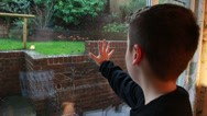 Stock Video Footage of Boy presses hand against window. wet outside