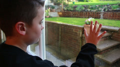 Boy looking out of window at miserable weather Stock Footage