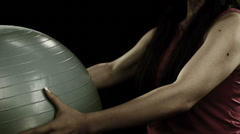 Woman uses exercise ball to do arm squeezes Stock Footage
