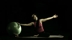 A woman uses a fitness ball to help stretch. Stock Footage