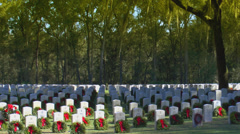 Driving by military gravestones decorated with wreaths cemetery Stock Footage