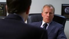 Businessman interviews new employee about his credentials - stock footage