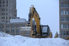 Excavator on snow covered mound of rubble. Stock Photos