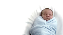A newborn baby wrapped up in a blue blanket resting. Stock Footage