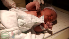A new born baby is being checked to make sure it is healthy Stock Footage