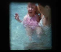 Mom with newborn Infant girl kicking feet in pool - stock footage