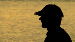 Close up of a man casting his rod and reel at sunset. Silhouetted fly fishing Stock Footage