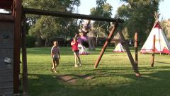 KIDS SWINGING IN ROCKY MOUNTAINS - stock footage