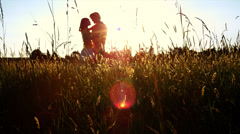 A silhouetted couple hug, kiss and then walk in a wide open field at sunset - stock footage