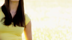 Woman stands in a field with the sunlight behind her playing with her hair - stock footage