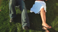 A cute young couple lays in the park grass and plays footsie with each other Stock Footage