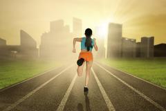athlete running on the track - stock photo