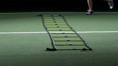 A group of athletes jump back and forth across turf practicing speed and agility - stock footage