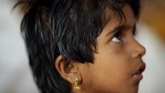 Closeup of young Indian girl with bindi and earirngs singing in class Stock Footage