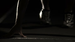 A male athlete runner gets himself set at the starting line of a track Stock Footage