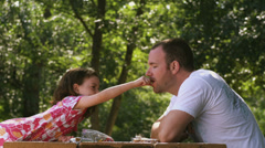 Family in Park -- Daughter feeds Dad crackers at a picnic table - stock footage