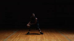 A solo basketball player does some dribbling moves in front of the camera Stock Footage