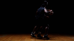 A basketball player challenges a defender and tries to dribble the ball past him - stock footage