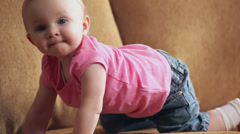 A cute baby girl moves around a couch Stock Footage