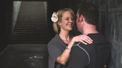 A couple stands in an alley and hug and kiss Stock Footage