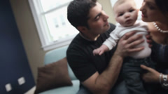 A young man and woman hold, kiss, and play with their baby Stock Footage