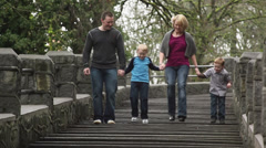 A family of four walk down some steps in a park Stock Footage