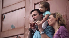 A young family smiles and stands in front of a door on a side street Stock Footage