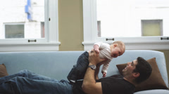 A man lays on the couch and lifts a baby above his head into the air Stock Footage