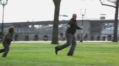 A father runs through the grass, blowing bubbles as his young son chases him Stock Footage