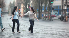 Two friends hold hands and walk when a third friend surprises them from behind Stock Footage