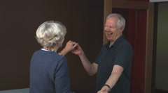 An older couple dance and laugh inside of their house Stock Footage