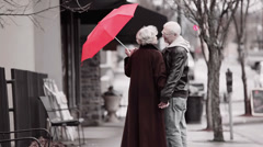 A cute old couple walk down the street under a red umbrella holding hands Stock Footage