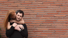 A young couple hug and kiss while standing in front of a brick wall Stock Footage