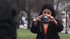 A couple hugs and takes a self portrait with their camera in the park Stock Footage